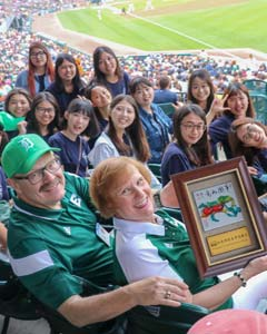 EMU President James Smith, his wife Connie, and asian female student pose for a photo at Tiger Stadium.